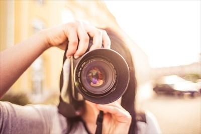 カメラのレンズを向けている女性